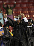 St. Augustine's College graduate Timothy Bias of Washington, D.C., celebrates on stage at Dorton Arena while his sister, Camille Bias, background, celebrates at her seat during St. Augustine's graduation ceremony.