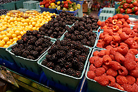 Boxes of blackberries, raspberries and golden berries for sale in the Granville Island Public Market, Vancouver, British Columbia, Canada