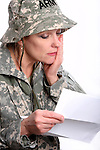 A sad USA military woman soldier reading a letter from home