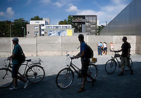 Tourists on bicycles at the Berlin Wall Memorial.