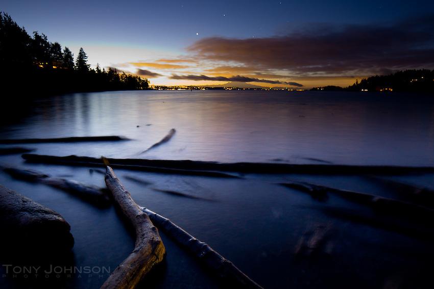 artificial lights illuminate driftwood and the distant sky over the beach on Bainbridge Island