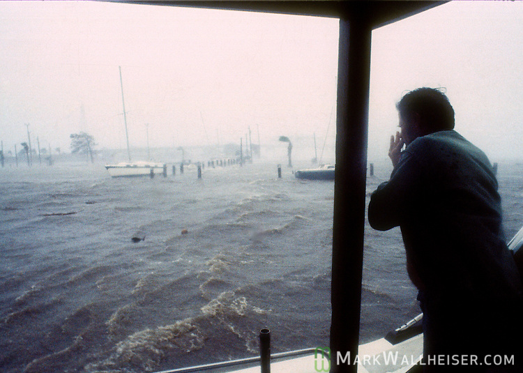 A man watches the storm surge from his boat during Hurricane Kate in the Apalachicola boat basin in Apalachicola, Florida November 21, 1985.  Kate, a late November Hurricane,  was latest forming Atlantic hurricane on record at the time and was the second for the area following Hurricane Elena two months earlier.