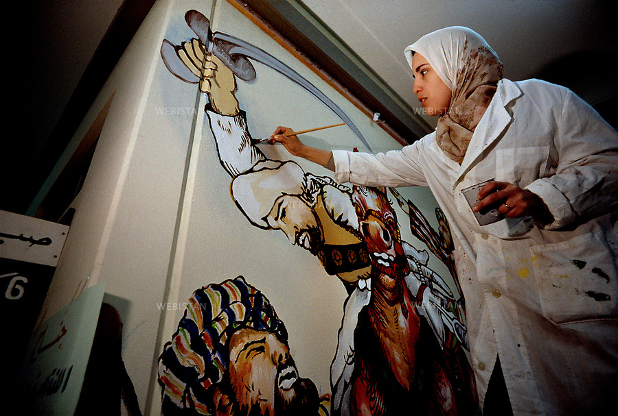 2000. A painting teacher paints on a wall at the Altakadum school built in 1988 in Tripoli. Une enseignante en peinture peint une fresque murale à l'Ècole Altakadum construite en 1988 à Tripoli.