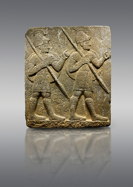 Hittite monumental relief sculpted orthostat stone panel from the Herald's Wall. Basalt, Karkamıs, (Kargamıs), Carchemish (Karkemish), 900-700 B.C. Military parade with soldiers. Anatolian Civilisations Museum, Ankara, Turkey<br /> <br /> Two helmeted soldiers marching soldiers in short skirts carry the shield on their backs and the spears in their hands.
