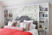 Wallpaper illustrating a 19th century German map of Paris adorns the wall behind this bed