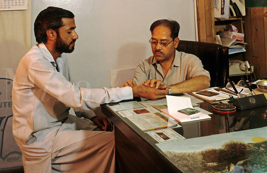 Pakistan. Doctor examining patient in his consulting room.