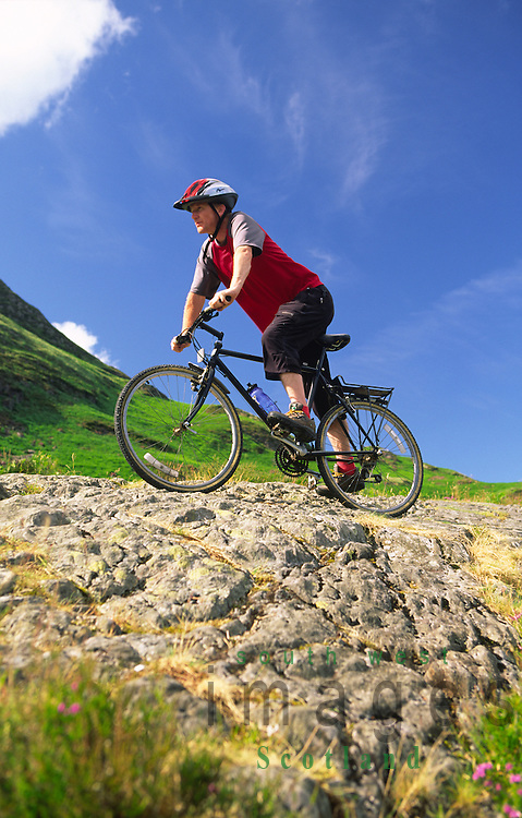 Summer mountain biker at Bruces Stone Glen Trool in the Galloway Forest Park Scotland UK