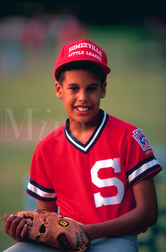Portrait of African American boy in little league baseball uniform.