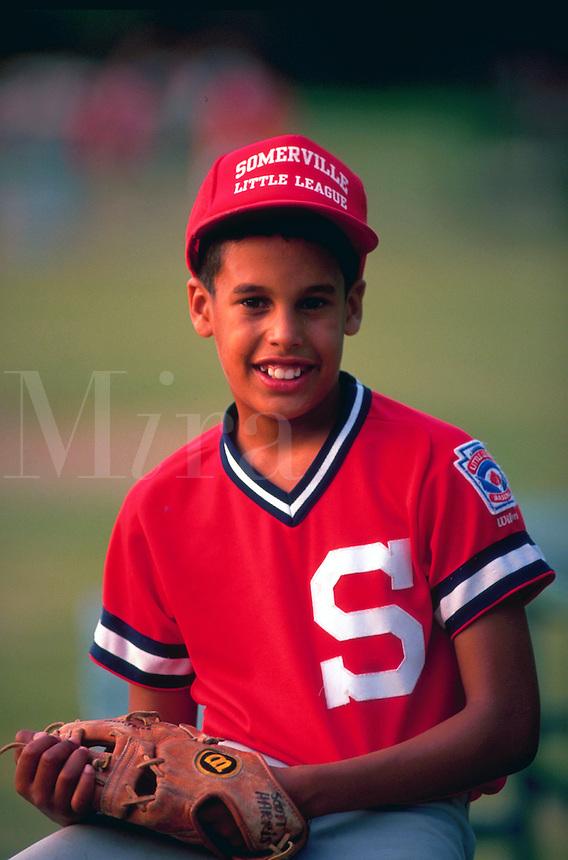 Portrait of African American boy in little league baseball uniform.