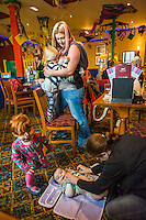 A mother breastfeeds her two year old daughter with her twelve week old baby asleep in a sling on her back.in the family restaurant and play area of a pub. The mother is standing and the boy is feeding while standing on a chair. In the foreground another mother is changing a nappy.<br /> <br /> Lancashire, England, UK<br /> <br /> Date Taken:<br /> 07-01-2015<br /> <br /> &copy; Paul Carter / wdiip.co.uk