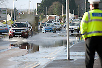 Thursday 02 January 2014<br /> Pictured:A police officer looks on as traffic makes it's way trough flood water on Carmarthrn's Coracle Way<br /> Re: The river that flows through the centre of Carmarthen has burst its banks after the recent bout of heavy rain.