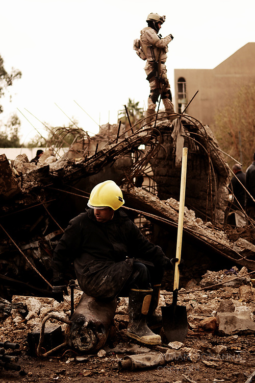 Baghdad, Iraq  : Tues 8th Dec 2009 :..A rescue worker and soldier sit and stand amongst the rubble of Iraq's Interior Justice Ministry..Devastating bomb attacks killed at least 112 in the Iraqi capital on Tuesday morning..Ayman Oghanna For The Times