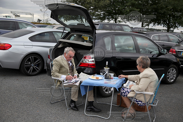 A couple have a picnic in the car park at Newmarket Races.