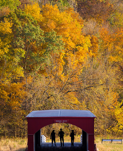 A trio of visitors stroll Roseman Bridge, one of Madison County's six remaining historic covered bridges as Fall colors bloom west of Winterset, Iowa.  ©Christopher Gannon/Ganon Visuals