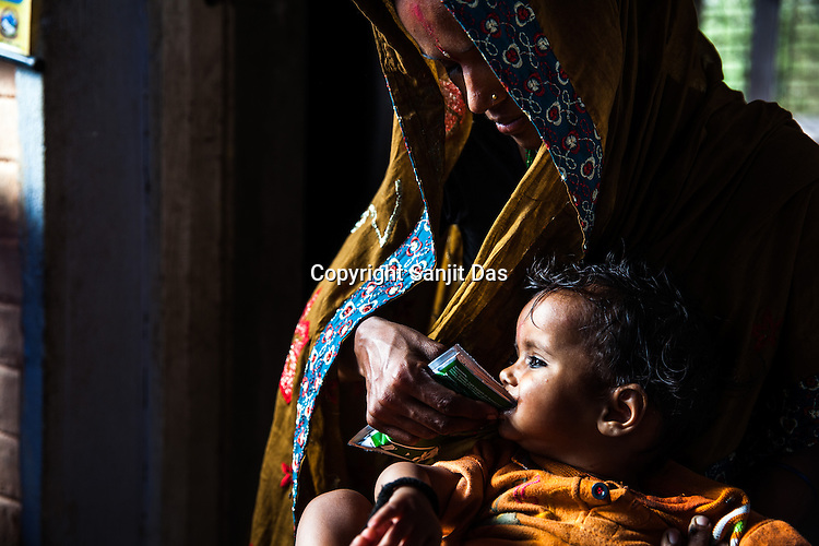 A woman feeds a sachet of RUTF to her son at the government health centre in  Hanuman Nagar, Saptari, Nepal.