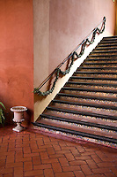 A terracotta tiled staircase with a handrail decorated with a garland of boxwood in the hallway of the Hacienda Benazuza, Sanlucar La Mayor, Spain
