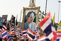 Un immense portrait du roi Bumibhol sur la place du monument de la Victoire pendant une manifestation des partisans du gouvernement et de la monarchie (Chemises jaunes) contre la r&eacute;volte des Chemises rouges qui occupent Bangkok en ce mois d'avril 2010. L'image intouchabele du roi est instrumentalis&eacute;e de part et d'autre, les chemises jaunes accusant les rouges de mettre en p&eacute;ril la monarchie.<br /> <br /> Eng:<br /> A giant portrait of the king Bumibhol surrounded by Yelllow shirts militants hanging the national flag. Supporters of the government and royalists use the king image and patriotic symbols to express their opposition to the Puea Thai party and Red shirts movement that they accuse to be a danger for the kingdom. Bangkok, Victory monument, 25 April 2010.