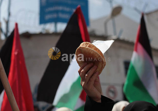 A Palestinian woman holds a bread during a protest a the decision made by the United Nations Relief and Works Agency (UNRWA) to reduce food aid delivered to the Gaza Strip in front of the UNRWA headquarters in Gaza City on April 9, 2014. Photo by Ashraf Amra