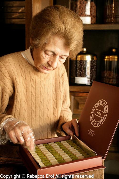 Meshur Bebek Badem Ezmesi in Bebek, Istanbul, Turkey: the owner fills a box of almond fondants