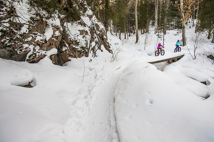 Winter cyclists on fat bikes ride snow trails along the Dead River in Marquette, Michigan.