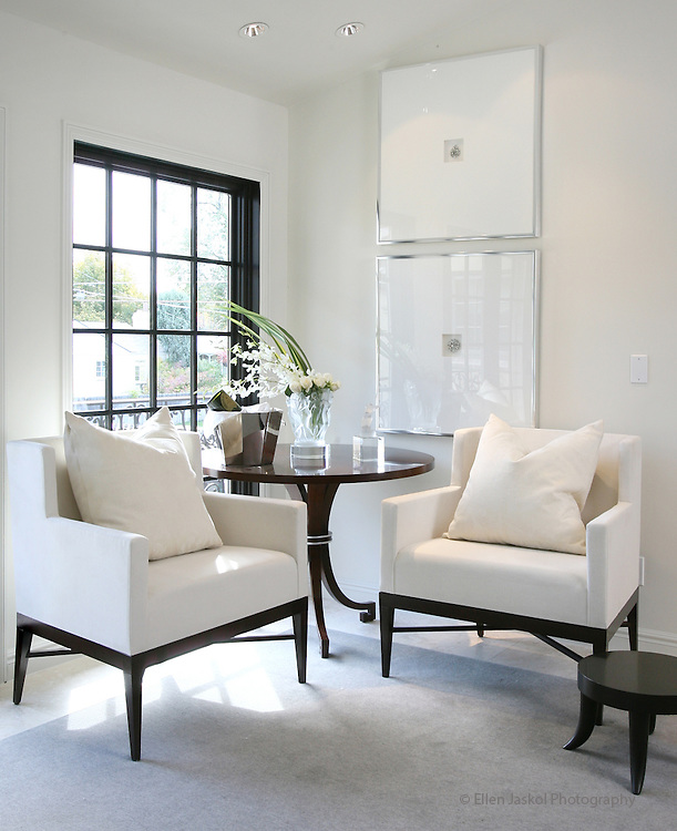 Framed antique brooches and modern clean white chairs create a calm sitting area in the bedroom. We visit the home of John Moinzad and David Hintgen, the owners of the home decor store, Aera.