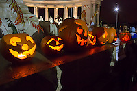 Participants watch pumpkin lanterns on display during a Halloween Festival in Budapest, Hungary on October 27, 2012. ATTILA VOLGYI