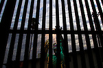 A Border Patrol employee welds wire mesh onto the US side of the border fence in Calexico, CA on Friday, April 14, 2006. The mesh makes it harder for migrants to climb the fence, a frequent occurence.<br />