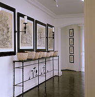 Old English prints of tree specimens hang above a Giacometti-style table on which stands a row of shell-encrusted bowls