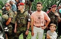 In der Ortschaft Krushe Te Vogel wurden 14 Kosovo-Albaner von serbischem Militaer / Sondereinheiten ermordet. Nachdem das Massengrab gefunden und geoeffnet wurde, fand die von der UCK organisierte Beerdigung durch Angehoerige und Freunde auf einem Feld nahe der Ortschaft statt.<br /> Hier: Ein Gefangener Kosovo-Albaner darf fuer die Beerdigung unter Polizeibewachung aus dem Untersuchungsgefaengnis.<br /> Krushe Te Vogel/Jugoslawien, 1.8.1999<br /> Copyright: Christian-Ditsch.de<br /> [Inhaltsveraendernde Manipulation des Fotos nur nach ausdruecklicher Genehmigung des Fotografen. Vereinbarungen ueber Abtretung von Persoenlichkeitsrechten/Model Release der abgebildeten Person/Personen liegen nicht vor. NO MODEL RELEASE! Don't publish without copyright Christian-Ditsch.de, Veroeffentlichung nur mit Fotografennennung, sowie gegen Honorar, MwSt. und Beleg. Konto: I N G - D i B a, IBAN DE58500105175400192269, BIC INGDDEFFXXX, Kontakt: post@christian-ditsch.de<br /> Urhebervermerk wird gemaess Paragraph 13 UHG verlangt.]