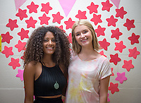 New roommates Anna Palmer '19, left, and Makenzie Nohr '19 take a moment to pose for a picture near a wall decoration of a heart in Pauley Hall on move in day, Aug. 21, 2015.<br />