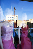 Eritrea. Maekel province. Asmara. A building, a man walking and two cars parked on the street are reflected in a shop window which rents marriage veils. © 2006 Didier Ruef