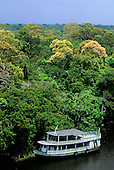 Amazonas State, Brazil. Typical Amazon riverboat with the green rainforest behind.
