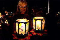 A woman holds two paper lanterns at the annual bon dance and Toro Nagashi (ìfloating lanterns set out to seaî) ceremony in Haleiwa. Inscribed with the names of the departed, the lanterns ride the outgoing tide to greet visiting spirits.