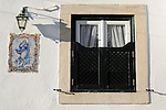 A window with green shutters, a small lamp, and decorative tiles in Sintra, Portugal.