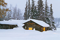Historic log cabin laden with fresh snow in the small community of Wiseman, Alaska.