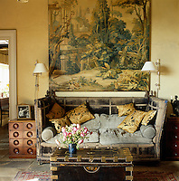 A large 19th century tapestry cartoon hangs above a vast antique Knole sofa in the living room