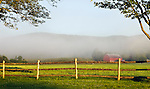 A dawn fog rolls across a Vermont farm at dawn