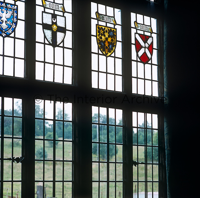 In the entrance hall of an English country house coats of arms in stained glass decorate the mullioned window