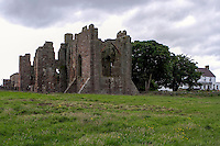 Lindisfarne Priory ruins and Manor House Hotel looking from beach towards Holy Island village