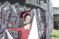 Female model wearing red tricot, holding a white fabric in her hands, while looking down concentrated.