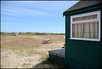 BNPS.co.uk (01202 558833)<br /> Pic: CorinMesser/BournemouthEcho/BNPS<br /> <br /> The sea glimps view from the beach hut. <br /> <br /> Britain's most expensive beach hut has gone on the market for a whopping 225,000 pounds - and it doesn't even come with sea views.<br /> <br /> The wooden shack, that measures 13ft by 13ft, looks out onto sand dunes and offers  glimpses of the sea. It is also right next to a public toilet block.<br /> <br /> The timber hut on Mudeford Spit near Christchurch, Dorset, is divided up into three rooms - a living area, bedroom and a mezzanine level.<br /> <br /> It has no bathroom, mains electricity or running water and requires a ride on a novelty land train or a 30 minute walk to get there.