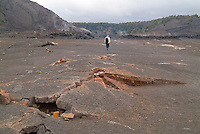 Broken lava sheets and hot steam from underground vents mark the trail for a male hiker across the floor of Kilauea Iki Crater, a 1959 lava lake, in Hawai'i Volcanoes National Park, Big Island.