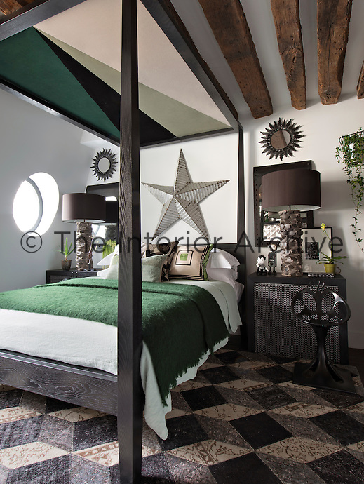 In the bedroom, a bold colour approach of black and shades of grey is offset with the single colour – viridian. A four-poster bed with canopy is draped with a green cover and pattern cushions.