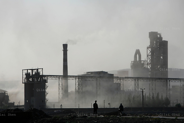 A man walks down a street near a cement factory in northern Ningxia Hui Autonomous Region on Friday, 18 May 2007.