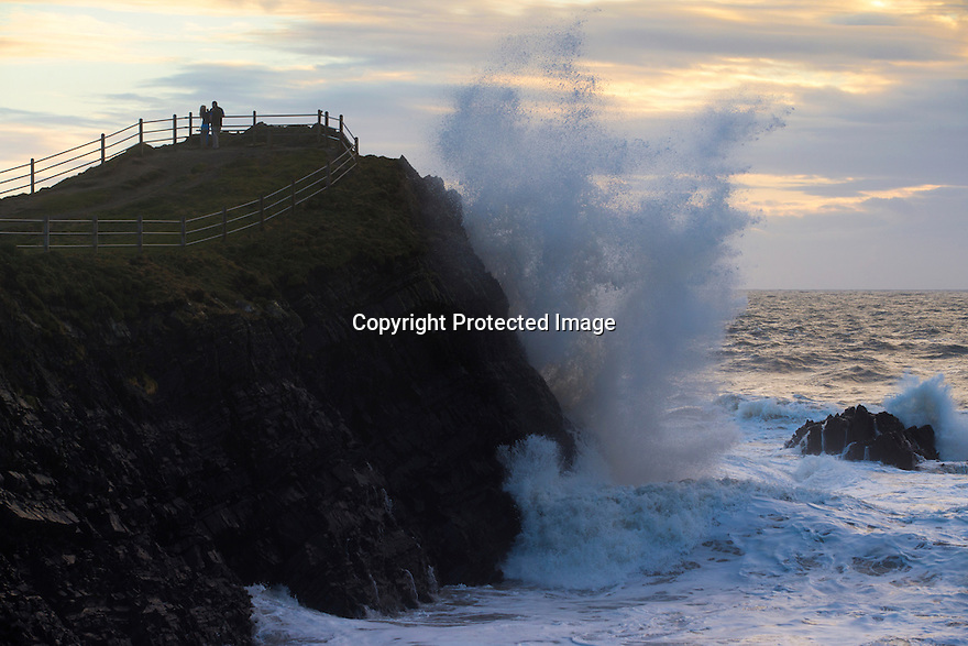 08/04/16 <br /> <br /> A couple watch as huge waves crash into Hartland Quay, North Devon, as strong winds and high tides help to set the dramatic scene.<br /> <br /> All Rights Reserved: F Stop Press Ltd. +44(0)1335 418365   +44 (0)7765 242650 www.fstoppress.com