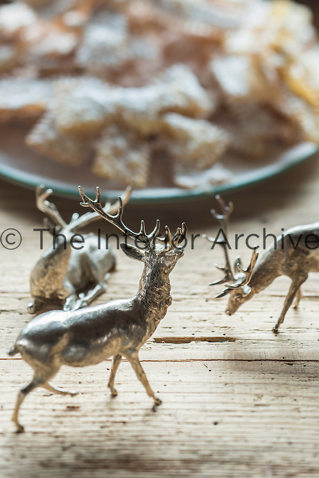 Detail of a small group of ornamental silver stags on a wooden dining table