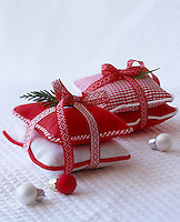 Handmade red and white lavender bags tied in pairs with a pretty ribbon and a sprig of cedar