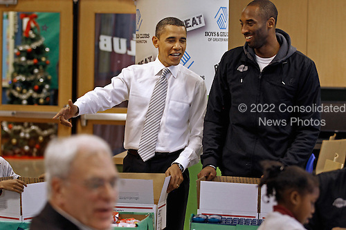 United States President Barack Obama (L) talks with Kobe Bryant of the Los Angeles Lakers while filling care packages during a NBA Cares service event at the Boys and Girls Club at THEARC, December 13, 2010 in Washington, DC. Bryant and all the members of the 2010 NBA Championship Lakers team volunteered on projects at the club before being honored by the president for their victory. .Credit: Chip Somodevilla - Pool via CNP