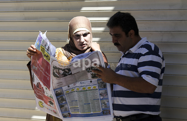 Palestinians read a local newspaper to find general secondary exams results in the West Bank city of Ramallah on July 22, 2010. Photo by Eyad Jadallah