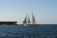 A sailing ship cruises the harbor at sunset between mainland Key West and Sunset Key.